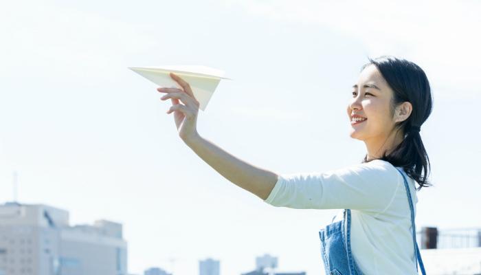 紙飛行機を飛ばす女性