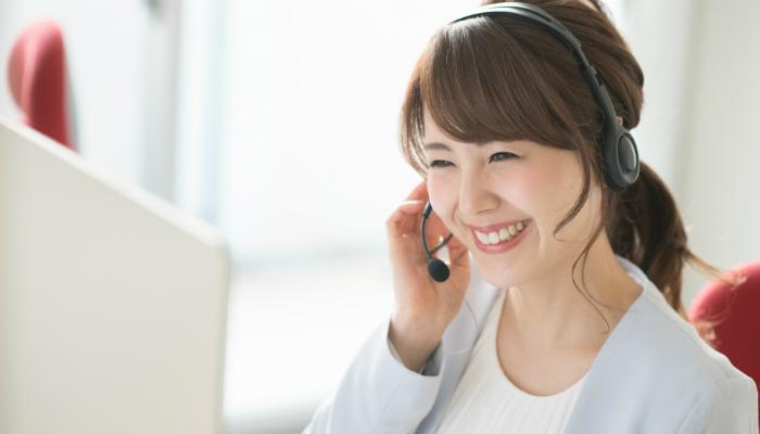 PCと電話する女性